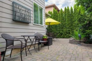 Gray patio with siding and furniture
